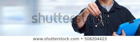 auto mechanic giving car key to man at workshop Stock photo © dolgachov