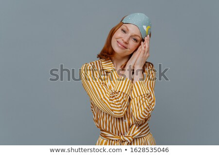 Beautiful relaxed woman tilts head on palms pressed together, looks at camera with satisfaction, enj Stock photo © vkstudio