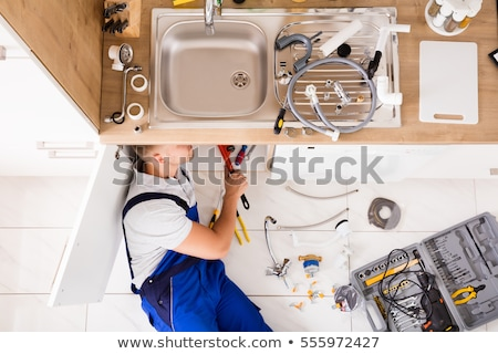 Male Plumber In Overall Fixing Sink Pipe Stock photo © AndreyPopov