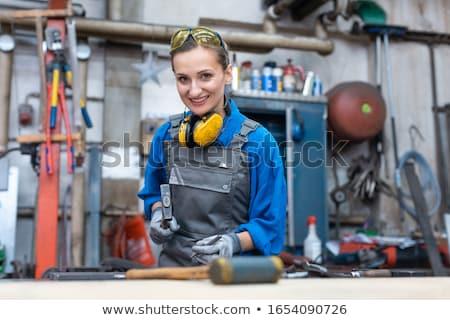 Woman worker marking workpiece in her workshop Stock photo © Kzenon