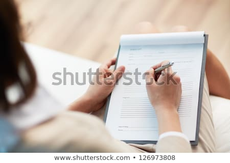 Medical professional filling in a patient record Stock photo © photography33