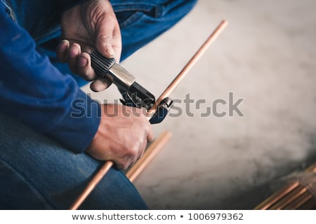 Stock photo: Plumber cutting copper pipe