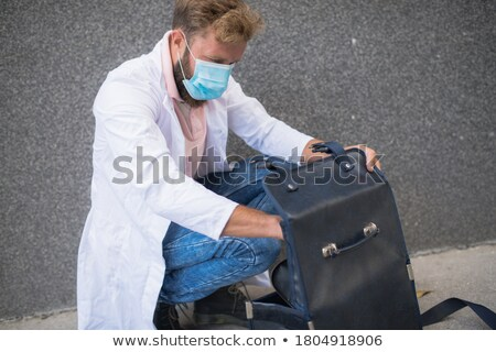 Smiling professional physician carrying clipboard Stock photo © stockyimages
