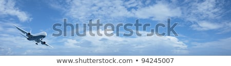 Foto stock: Jet In A Blue Cloudy Sky Panoramic Composition