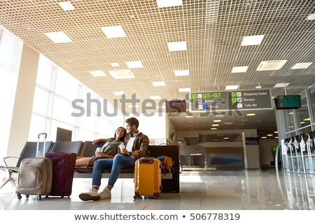 young couple with coffee cups sitting on suitcases stock photo © nejron