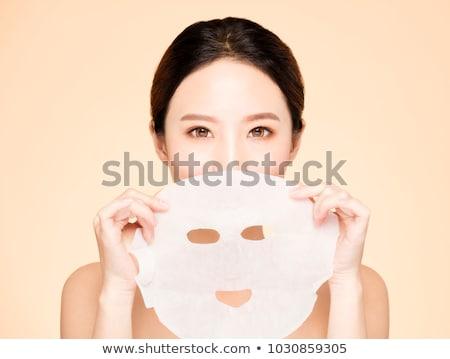 Prettyl woman with facial mask at beauty salon. Spa treatment Stock photo © Yatsenko