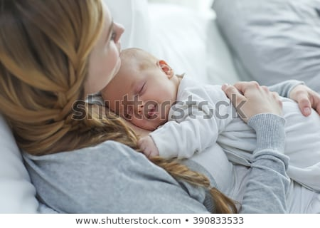 Mother smiling at baby lying on bed Stock photo © IS2