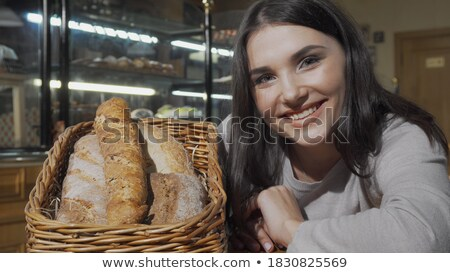 Smiling woman smelling a bakery snacks at counter Stock photo © wavebreak_media