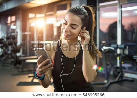 Smiling sports woman listening music by smartphone and looking away Stock photo © deandrobot