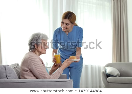 Foto stock: Nurse Serving Food To Senior Patient