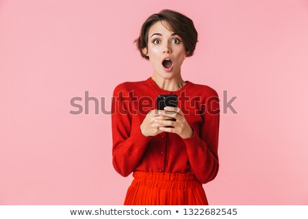 Portrait of excited woman 20s wearing casual clothing holding gi Stock photo © deandrobot