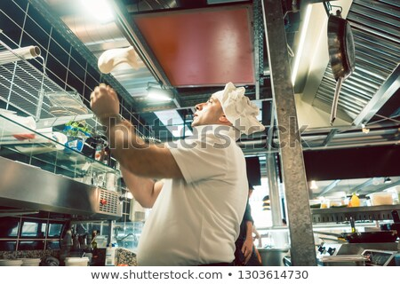 Stok fotoğraf: Cook Tossing Dough While Preparing Pizza In A Modern Italian Restaurant