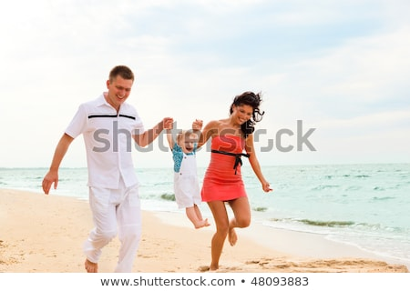 toddler girl running with their parents on sand at beach stock photo © andreypopov