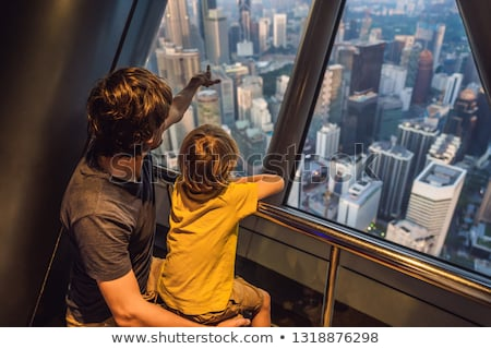 Dad and son are looking at Kuala lumpur cityscape. Panoramic vie Stock photo © galitskaya