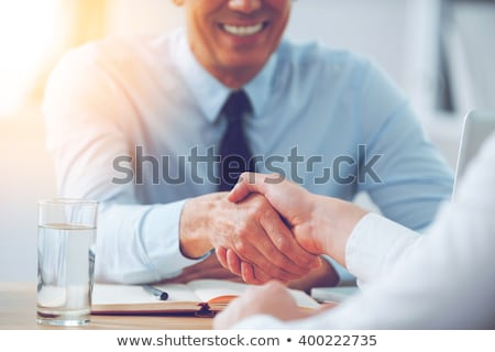 Close-up of two business people shaking hands while sitting at t stock photo © Freedomz