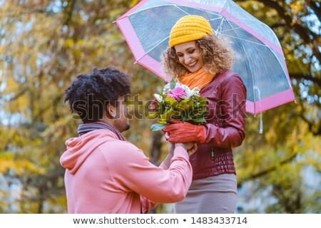 Black man proposing to Caucasian girl who happily accepts Stock photo © Kzenon