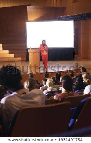 Front view of mixed race businesswoman giving speech in front of audience in the auditorium Stock photo © wavebreak_media