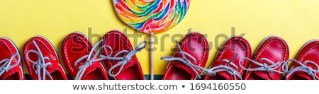 A lot of small red boat shoes near big multi-colored lollipop on colored background.  Top view, copy Stock photo © Illia