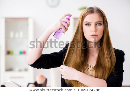 Young woman spraying hair polish to her hair Stock photo © Elnur