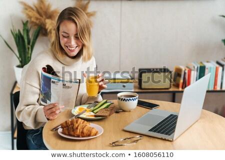 Fotografia uśmiechnięty czytania magazyn za pomocą laptopa Zdjęcia stock © deandrobot