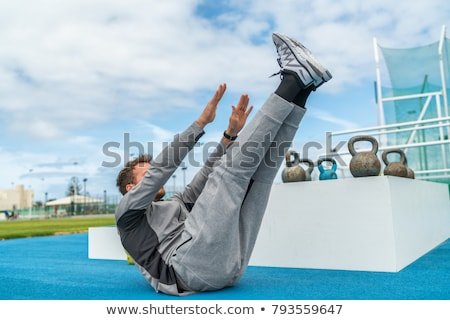 Abs exercise leg lift toe touch sit-up workout man strength training at fitness gym athletic stadium Stock photo © Maridav