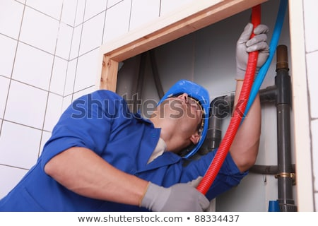 Plumber feeding flexible pipes behind a tiled wall Stock photo © photography33