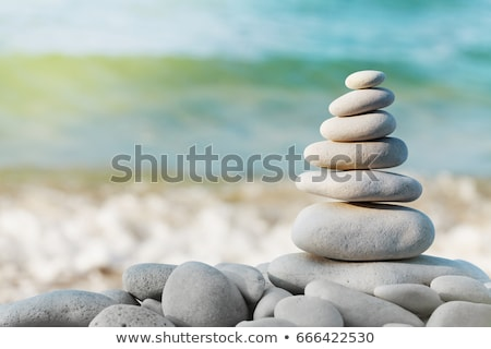 pebble stone pyramid against blue sea stock photo © rufous