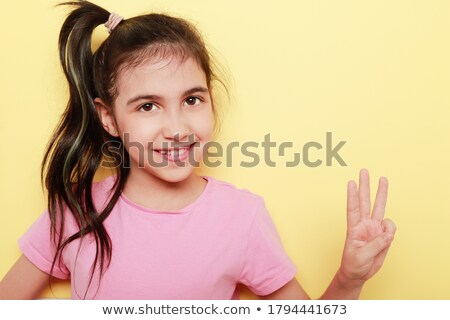 Beautiful young model raising her hand up and showing three fing Stock photo © get4net