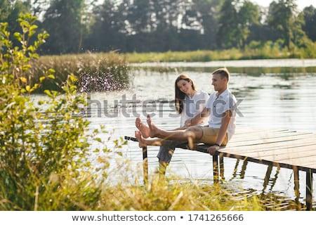 женщину сидят озеро реке скамейке девушки Сток-фото © DedMorozz