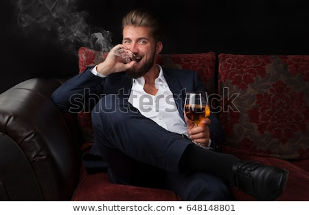 Attractive businessman smoking cigar and enjoying whiskey in office chair Stock photo © deandrobot