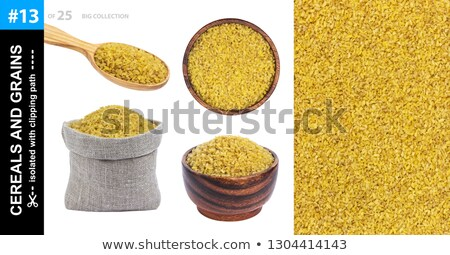 Bowl of bulgur porridge and spoon isolated. Healthy food for bre Stock photo © MaryValery