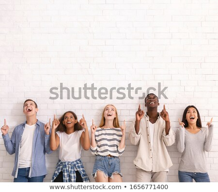 emotional excited group of friends pointing stock photo © deandrobot