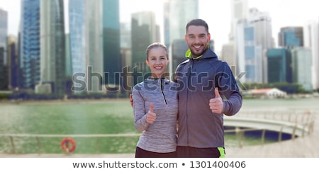 happy man showing thumbs up over singapore city stock photo © dolgachov