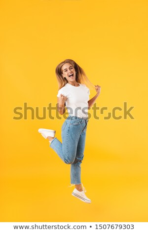 Image of pleased woman 20s wearing casual clothing screaming or  Stock photo © deandrobot