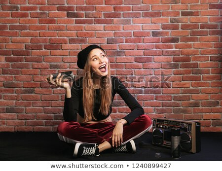Photo of joyous young hip hop girl, sitting on floor against bri Stock photo © deandrobot