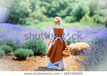 cute curly young girl standing on a lavender field in white dress stock photo © elenabatkova
