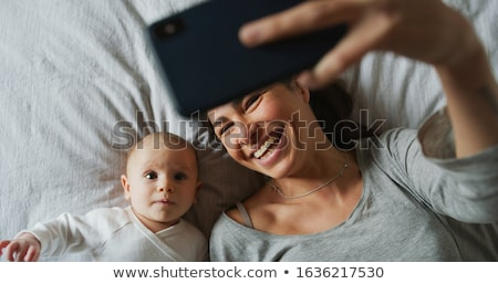 mother with baby calling on smartphone at home stock photo © dolgachov