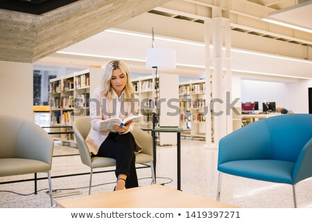 Serious student concentrating on reading book in library Stock photo © pressmaster