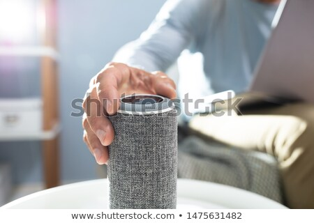 Man Adjusting Volume On Wireless Speaker Stock photo © AndreyPopov