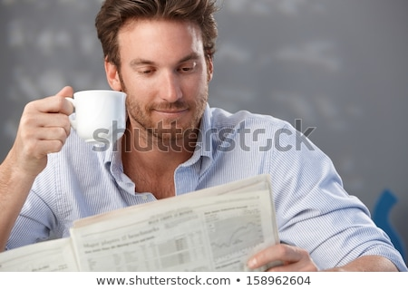 man reading newspaper and drinking coffee at home stock photo © dolgachov