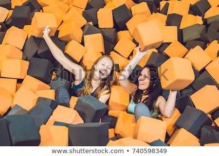Two young women having fun with soft blocks at indoor children playground in the foam rubber pit in  Stock photo © galitskaya