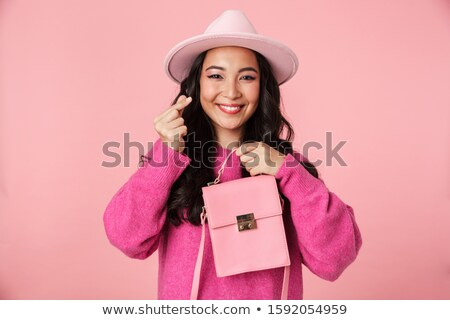 Image of asian girl showing money counting gesture and holding s Stock photo © deandrobot
