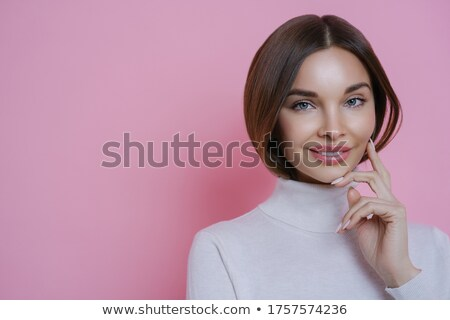 Happy dark haired woman with well groomed complexion, smiles tenderly, touches cheek, has manicure,  Stock photo © vkstudio