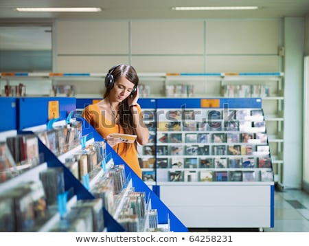 young woman in shop chooses disk stock photo © Paha_L