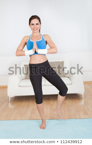 young fitness woman standing on a mat stretching her arms stock photo © Rob_Stark