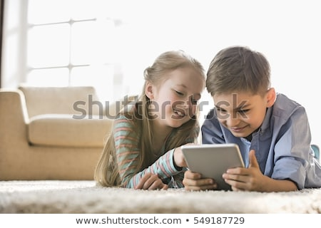 Happy pre-teen girl using a digital tablet computer Stock photo © vladacanon
