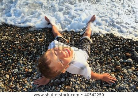 sitting teenager boy looking upwards on stone seacoast, wets fee Stock photo © Paha_L