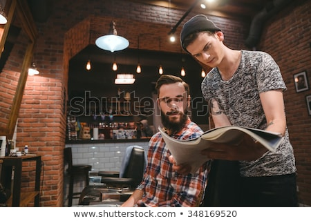 Young hairstylist and bearded client looking through magazine  Stock photo © deandrobot