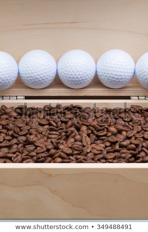 Coffee beans and golf balls in an open box Stock photo © CaptureLight