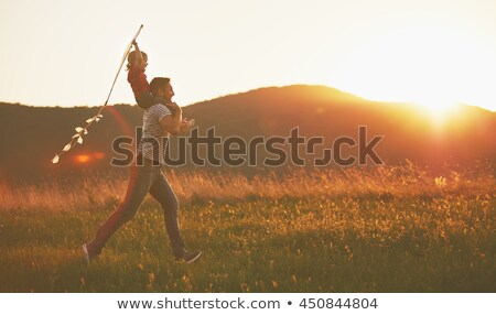 Man with girl on shoulders in a field Stock photo © IS2